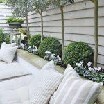 Banc de jardin blanc facon banquette avec coussins rayes et coussins pour assise