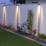 Jardin eclaire avec spots design et colonne chromee murale