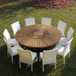 Jolie table de jardin ronde et ses nombreuses chaises blanches en resine