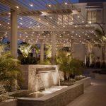 Mise en valeur d une belle terrasse avec luminaire suspendu guirlandes et eclairage d une fontaine