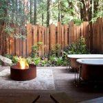 Petit brasero en fonte integre sur dalle dans jardin exterieur