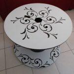 Table de jardin ronde bobine avec arabesque noire sur fond blanc