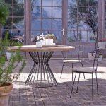 Table de jardin ronde scandinave en bois avec chaise noire design en plastique