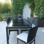 Table exterieure resine avec dessus de table en verre et ses 4 chaises avec coussin blanc